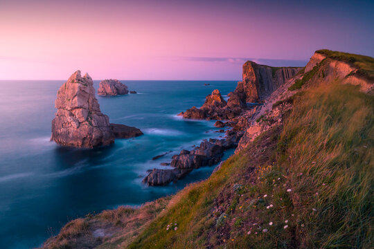 Breathtaking landscape of rocky cliffs in waving sea reflecting picturesque colorful sunset sky in Cantabria
