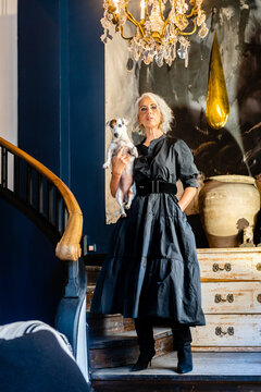 Full body of confident stylish middle aged female in elegant black dress holding little dog and looking at camera while standing near stairs in room with vintage furniture and chandelier at home