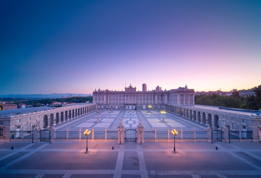 Magnificent scenery of Royal Palace of Madrid and empty square illuminated by street lamps in evening