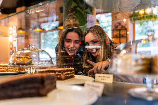 Young content women standing at counter in cafe and choosing delicious desserts while spending weekend together