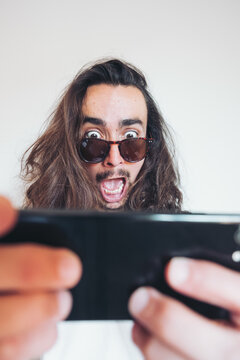 Overwhelmed young long haired hipster guy in sunglasses looking at screen of smartphone with astonished face expression while getting incredible news