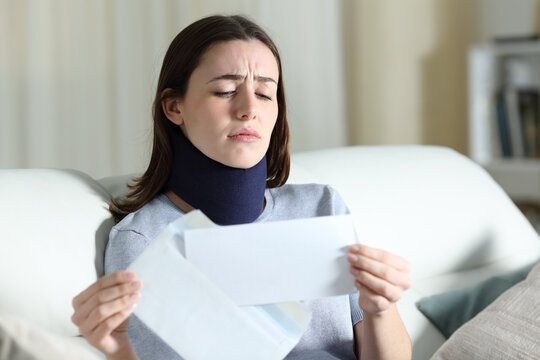 Sad disabled woman reading bad news on letter