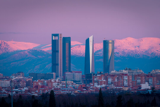 View of skyscrapers of Cuatro Torres Business Area on background of mountains lit by pink sunset light in Madrid