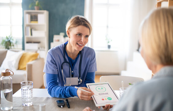 Caregiver or healthcare worker with senior woman patient, measuring blood glucose indoors.