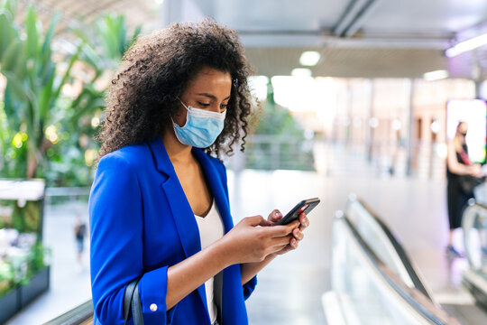 African American female wearing face mask in casual clothes standing in modern escalators and surfing Internet on smartphone