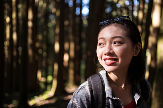 Smiling Asian female explorer with backpack standing in woods and admiring nature during summer adventure in Alishan Township