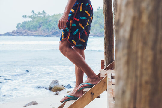 Side view of crop unrecognizable male traveler in colorful shorts standing on wooden steps near waving sea and enjoying summer holidays in Hiriketiya in Sri Lanka
