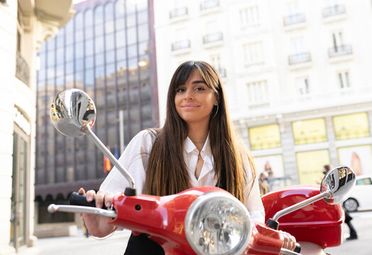 Confident young ethnic female with long dark hair in white shirt smiling and looking at camera while riding red scooter on city street