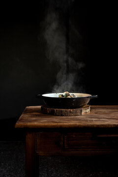 Frying pan with hot steaming freshly cooked dish placed on rustic wooden table against black background