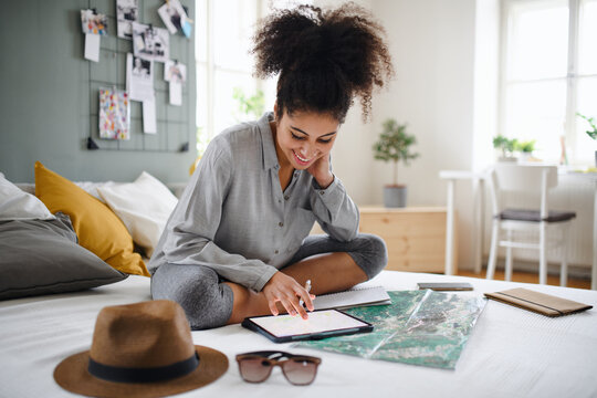 Young woman with tablet and map indoors at home, planning traveling trip.