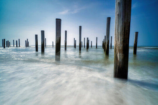 Long exposure seascape. Taken at the North Sea in Petten with the pole village in the sea, Blue sky, sun and shodows. Focus on foreground