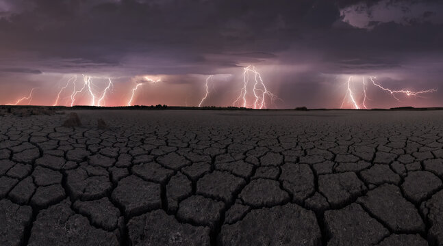 Dark thunderstorm sky with bright lightnings striking above drought cracked lifeless ground