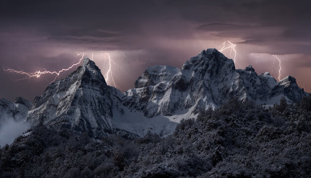 Scenery of mountain range covered with snow under thunderstorm sky with bright lightnings in winter