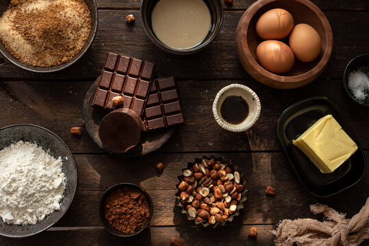 Top view set of various ingredients for sweet chocolate pastry with hazelnuts arranged on wooden table