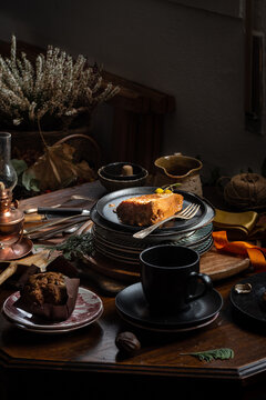 Piece of delicious pumpkin cake and whole chocolate muffin served on wooden table with tea set in dark room