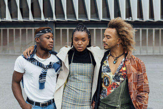 Group of serious unemotional young African American hipster friends in trendy outfits on urban street