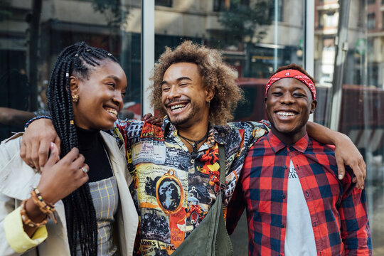 Group of cheerful young African American hipster friends in trendy outfits smiling happily on urban street