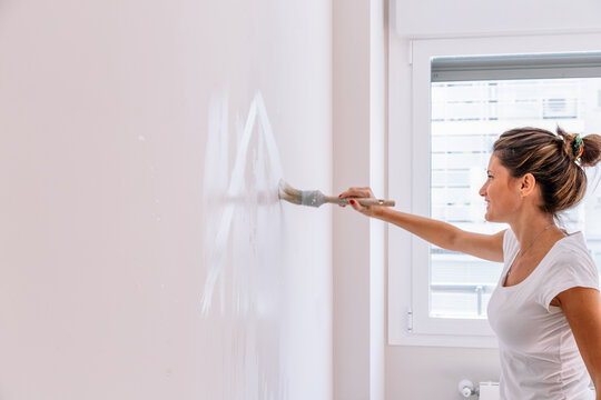 Side view of delighted young female smiling and smearing paint on wall during renovation at home