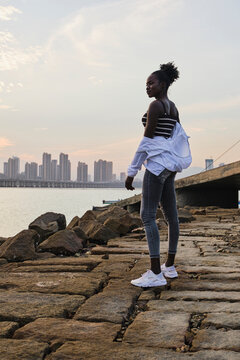 Full body side view of young African American female in casual outfit standing on stone city embankment near sea in sunset time