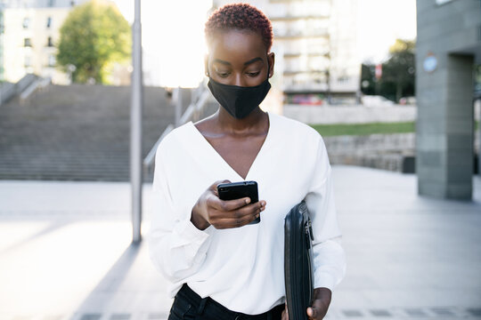 Stylish young African American businesswoman in protective mask standing on city street and messaging on smartphone