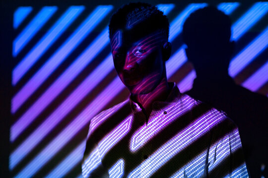 Unemotional African American male standing in neon light in shape of stripes in dark studio and looking at camera
