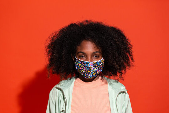 Young ethnic woman with Afro hairstyle wearing fabric mask and looking unemotionally at camera on red background
