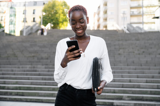 Young African American businesswoman in classy outfit reading message on smartphone and smiling satisfied with news while standing on stairway on urban street