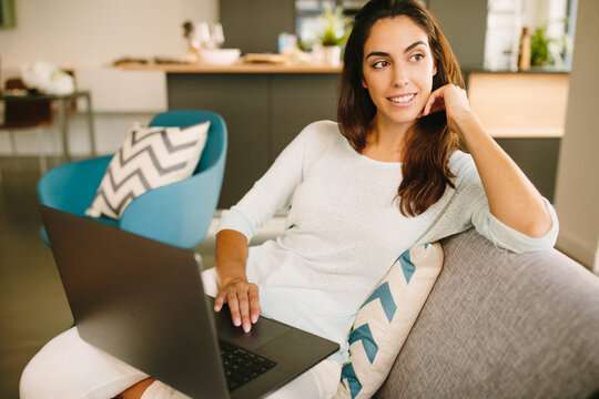 Young female freelancer in casual outfit sitting on sofa and using laptop while working remotely from home in living room