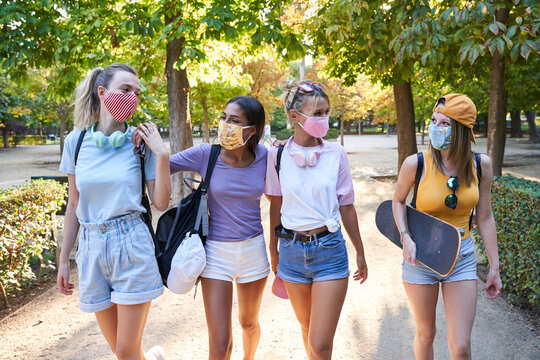 Cheerful trendy teen girlfriends in casual clothes and protective masks with backpacks and skateboard walking together in green park in sunny summer day