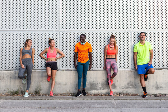 Group of cheerful multiethnic fit runners in sportswear leaning on wall of building while standing on street on sunny day