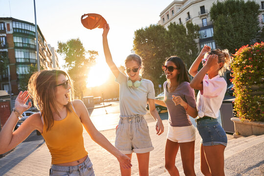 Happy carefree teen female friends in trendy clothes and sunglasses having fun and dancing together on urban street while enjoying summer day in city