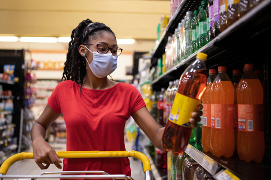 Afro latina young woman wearing a face mask reads the label in soda bottle while shopping in supermarket