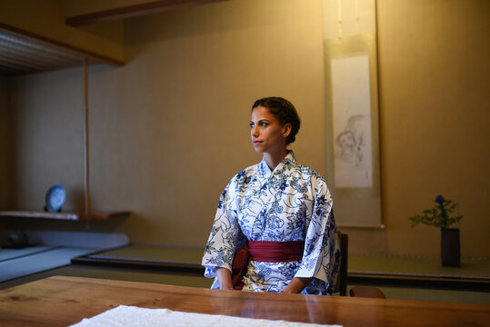Young caucasian woman in Japanese clothes sitting at the table in ryokan room and practicing mindfulness meditation