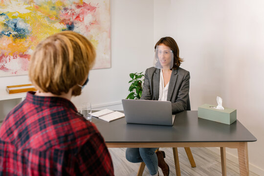Happy adult female psychologist in formal clothes and eyeglasses smiling while consulting unrecognizable bearded male patient sitting at table with laptop