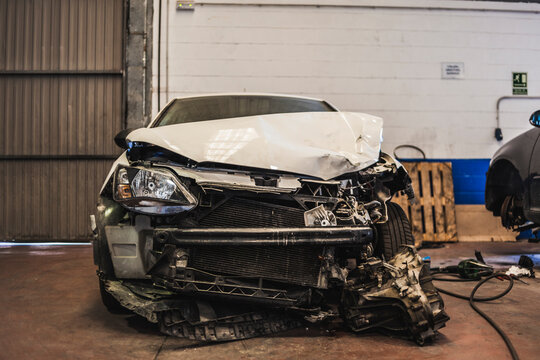 Modern vehicle with wrecked front parked inside spacious professional garage for repair works