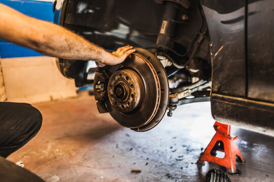 Unrecognizable technician with dirty hands installing clutch disc on engine while repairing vehicle in garage