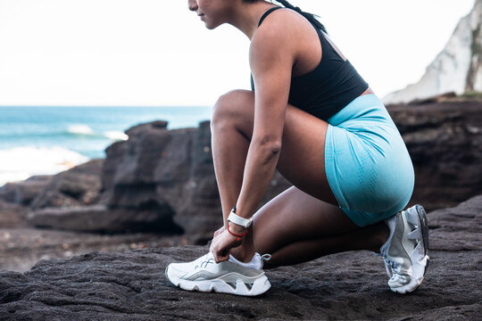 Side view of fit ethnic female athlete tying shoelaces on sneakers while sitting on seashore and preparing for workout
