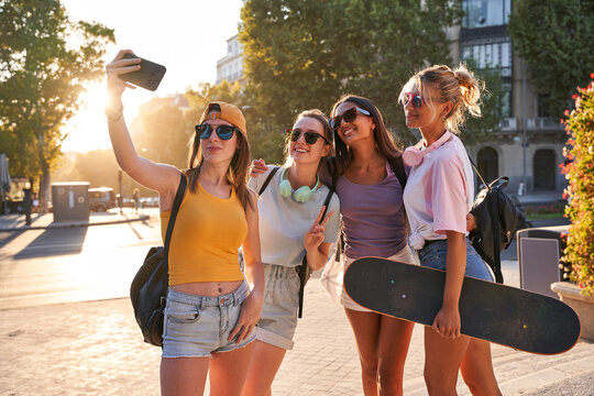 Cheerful trendy young multiracial girlfriends in sunglasses with backpacks and skateboard taking selfie on mobile phone while gathering together on urban square in summer day