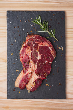 Top view of fresh uncooked rib eye beef steak with rosemary sprig and dried spices  on black slate board