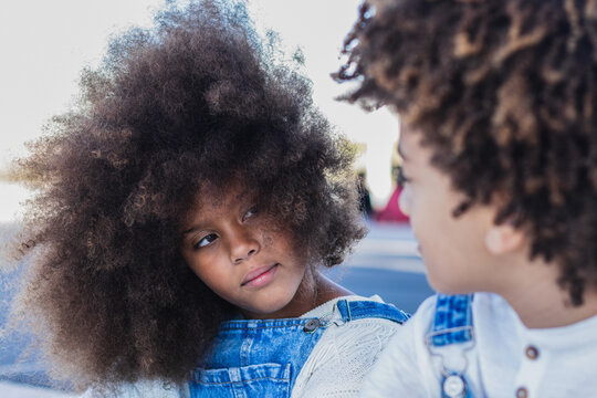 Teen black sister and brother with Afro hair wearing denim overalls sitting on urban street looking at each other