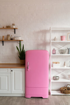 Kitchen shelves, wooden surface and pink fridge on white background. White kitchen interior counter top.