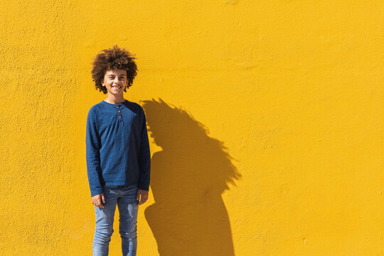 Positive male African American teenager with Afro hair looking at camera while standing against vivid yellow wall in sunlight