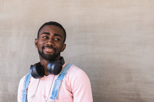 Cheerful African American male hipster in trendy clothes and with headphones on neck standing against concrete wall and looking away