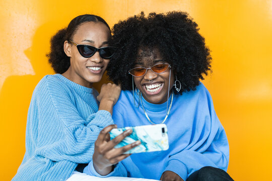 Cheerful young African American women in stylish sunglasses and lilac clothes taking selfie on mobile phone against yellow background