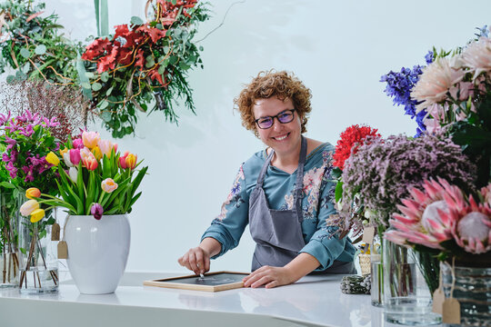 Cheerful female florist writing on black chalkboard preparing bright flower shop for Christmas holidays