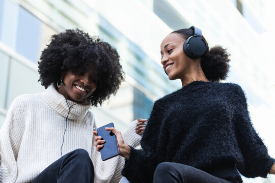 Low angle of positive young African American female friends with smartphone and headphones having fun and enjoying music while chilling together on urban street