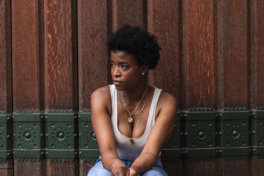 Young unhappy African American female with afro hair standing against wooden wall and thoughtfully looking away
