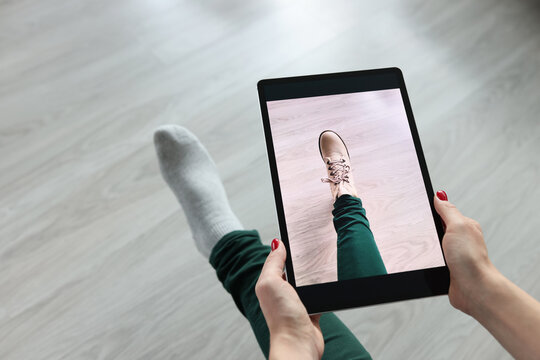 Woman holding tablet over her leg and trying on shoes closeup