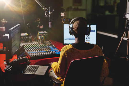 Back view of ethnic female in headphones sitting at table with mixing console and speaking in microphone while working in broadcast studio