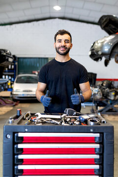 Cheerful male mechanic showing thumbs up while standing near tool cabinet with various instruments in car service and looking at camera